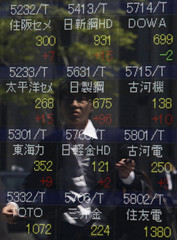 Pedestrian is reflected on stock quotation board showing stock prices outside a brokerage in Tokyo