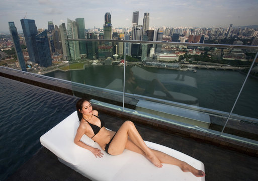 A model lies on a bed in the infinity pool of the Skypark that tops the Marina Bay Sands hotel towers in Singapore