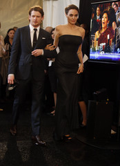 Jack O'Connell and Angelina Jolie enter the backstage press room during the Hollywood Film Awards in Hollywood