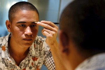 Xiao Jiguo, a 29-year-old actor from China's Sichuan province, shapes his eyebrows as he gets ready to impersonate U.S. President Barack Obama in a hotel room in the southern Chinese city of Guangzho