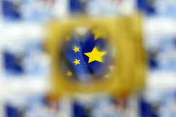 A part of the EU flag is pictured through a magnifying glass on a special edition of postage stamps in Belgrade