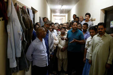 Asian workers gather as they speak to Reuters' journalists at their accommodation in Qadisiya labour camp, Saudi Arabia
