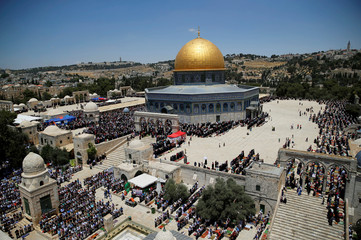 The Dome of the Rock is seen in the background as Palestinians pray on the second Friday of the holy fasting month of Ramadan on the compound known to Muslims as Noble Sanctuary and to Jews as Temple Mount, in Jerusalem's Old City