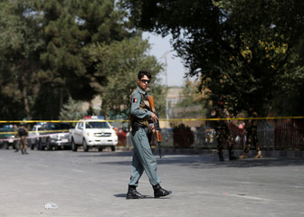An Afghan policeman stands guard at the site of abomb blast near the U.S. Embassy in Kabul, Afghanistan
