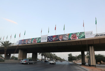 U.S. President Donald Trump's and Saudi Arabia's King Salman bin Abdulaziz Al Saud's photos are seen with flags of both countries on Mecca Road as part of celebrations to welcome United States President Donald Trump, in Riyadh