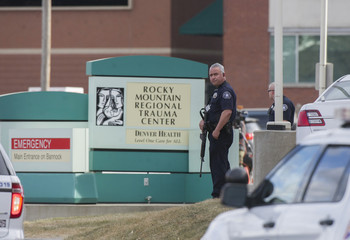 A police officer stands watch outside the Rocky Mountain Regional Trauma Center after a shooting at a motorcycle show in Denver, Colorado