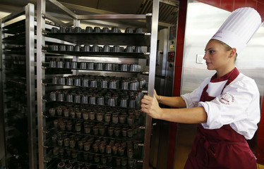 A pastry chef pushes into an oven trays of caneles, a small French pastry, at the Maison Baillardran cake shop in Bordeaux