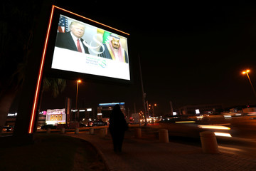 A woman passes by under a LED out-door screen with U.S. President Donald Trump's and Saudi Arabia's King's Salman bin Abdulaziz Al Saud's photos on Mecca Road as part of celebrations to welcome United States President Donald Trump, in Riyadh