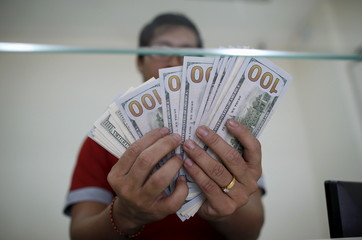 Bank staff shows U.S. hundred dollars bills at AYA Bank's money changer in Yangon