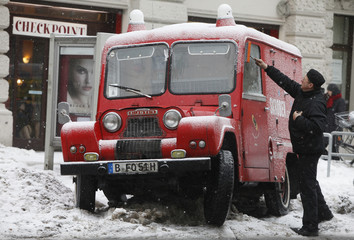Chimney sweeper cleans the windows of his car as freezing rain falls in Berlin