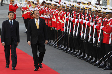 Thailand's Prime Minister Abhisit Vejjajiva and Philippine President Benigno Aquino III review an honor guard at the Government house in Bangkok
