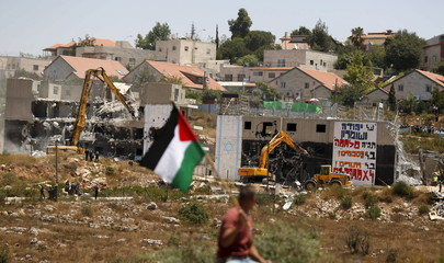 Palestinian man holds a Palestinian flag as Israeli heavy machinery demolish vacant apartment blocs by order of Israel's high court, in the West Bank Jewish settlement of Beit El near Ramallah