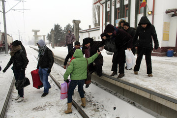 People rush to board a train at Lehliu railway station
