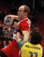Austria's Schlinger tries to score past Brazil's Kojoroski during their group B match at the Men's Handball World Championship in Norrkoping
