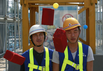 Mock bricks and plastic balls fall on participants during a course to demonstrate the danger of falling objects at an experience centre for construction safety training in Beijing