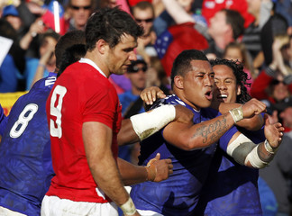 Samoa's Anthony Perenise celebrates after scoring a try as Wales' Mike Phillips reacts during their Rugby World Cup Pool D match at Waikato Stadium in Hamilton