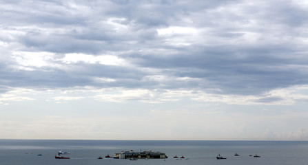 Tug boats tow the Costa Concordia ship as they arrive outside Genoa's port, in northern Italy, where the ship will be broken up for scrap