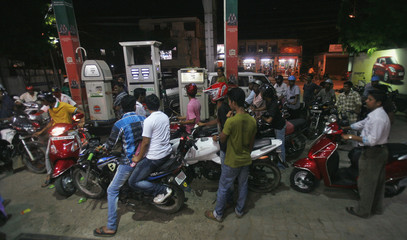 Motorcyclists crowd a fuel station to fill up on petrol in Agartala