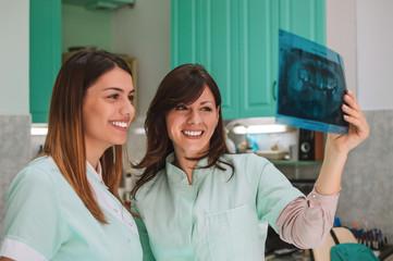 Two beautiful female dentists watching x-ray.