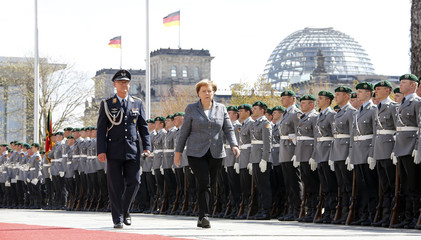 German Chancellor Merkel walks past a guard of honour at the Chancellery in Berlin