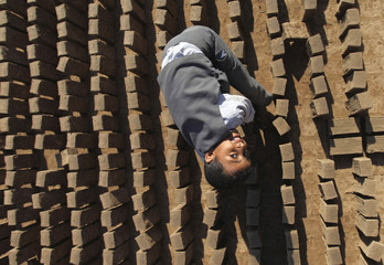 A boy smiles as he works with mud bricks at a traditional brick-manufacturing site in Sanaa
