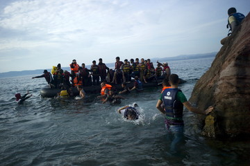 Refugees and migrants jump off a dinghy as they arrive on the Greek island of Lesbos