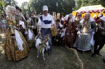 Winner goat Demyte pose for a picture with owner Ferdinandas Petkevicius during the goat beauty pageant in Ramygala, Lithuania