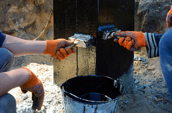 Contractor workers painting black coal tar or bitumen at concrete surface by the brush, A waterproofing. Foundation Waterproofing, Damp proofing Coatings.