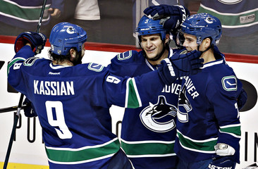 Vancouver Canucks' Bieksa is congratulated by teammates Kassian and Hamhuis after scoring against the Minnesota Wild in their NHL hockey in Vancouver