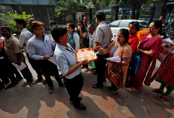 A bank employee offers drinking water to people as they wait to enter ICICI bank in Kolkata