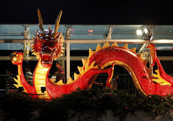 People walk past a dragon decoration on a pedestrian overhead bridge ahead of the Lunar New Year in Singapore