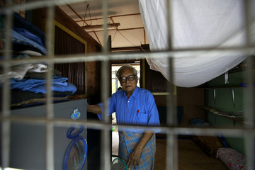 Win Tin poses in his prison issued shirt at his home in Yangon