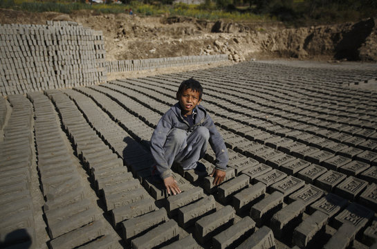 Rahul, flips bricks laid out to dry out before packing them in brick factory in Kathmandu