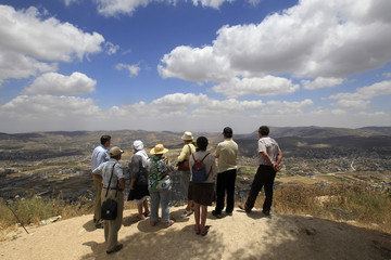 Tourists stand at a lookout point on Mount Gerizim during a tour of Jewish settlements in the West Bank