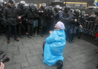 A protester kneels in front of police during a rally in support of EU integration in Kiev