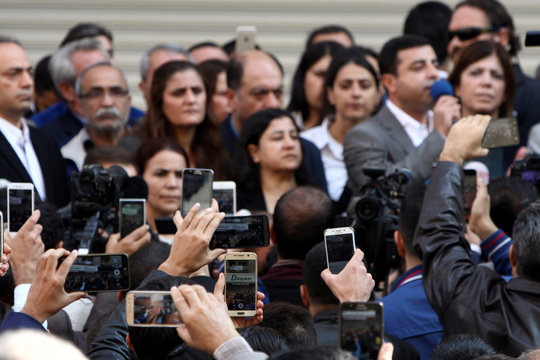 People record with their smartphones as Selahattin Demirtas talks during a gathering to protest against the arrest of the city's two joint mayors on terrorism charges in Diyarbakir