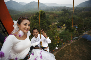 A couple smile for a picture at the top of a climing wall during their wedding ceremony in Ratchaburi