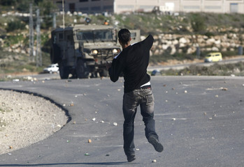 A Palestinian protester throws a stone at Israeli troops during a demonstration near the Jewish settlement of Halamish