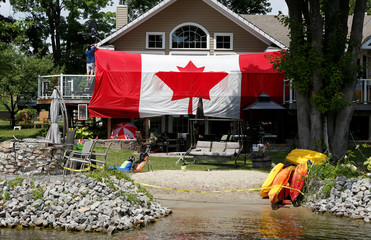 A man hangs a large Canadian flag on the deck his cottage to celebrate Canada Day in Rideau Ferry
