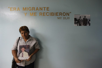 Olga Navarro holds a picture of her son Lenis Mejia, an illegal immigrant who went missing in 1996, after a mass in Tegucigalpa