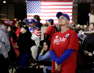 Supporters watch election results on a screen as they wait to see Democratic U.S. presidential candidate Bernie Sanders speak during an election night rally in Santa Monica, California