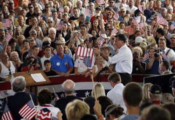 Republican presidential candidate and former Massachusetts Governor Mitt Romney takes the stage at a campaign rally at the Military Aviation Museum in Virginia Beach