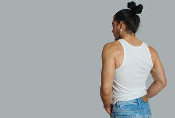 Young hispanic male with gathered hair done bow in white sleeveless t-shirt, seen from behind