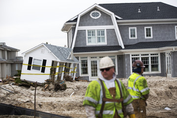 Workers stand in front of home damaged by Superstorm Sandy while building levee to protect homes in Mantoloking, New Jersey