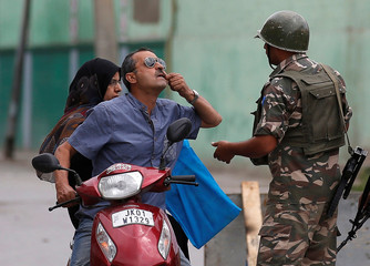 A man shows his tooth to an Indian policemen as he seeks permission to see a doctor after he was stopped during a curfew in Srinagar