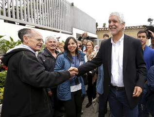 Enrique Penalosa, mayoral candidate for Bogota, greets a supporter after casting his vote during local and regional elections in the capital of Colombia