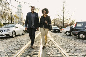 Low angle portrait of smiling couple holding hands and walking on street against clear sky