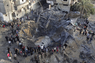 Palestinians gather around a destroyed house after an Israeli air strike in Khan Younis in the southern Gaza Strip