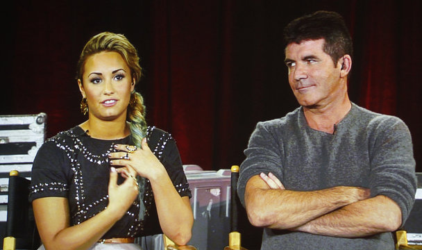 """Judges from the reality series """"The X Factor"""" Lovato and Cowell are pictured on a video screen via satellite from Miami at the Fox television network portion of the Television Critics Association Summer press tour in Beverly Hills"""