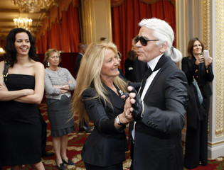 Ricky Lauren, wife of US fashion designer Ralph Lauren, dances with German fashion designer Lagerfeld during a ceremony at the Elysee Palace in Paris